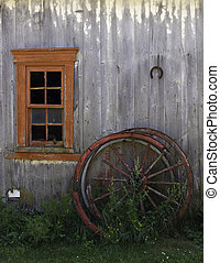 Rustic Red Window - Red window and wagon wheels on an old...