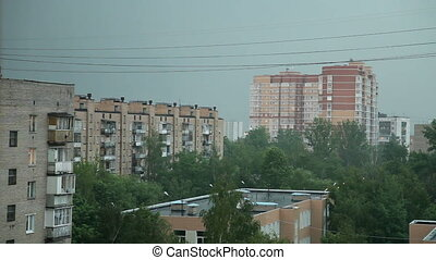 Heavy rain with thunderstorm in the city. Sometimes a flash of lightning.