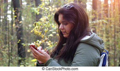 Young smiles woman uses the phone in the autumn forest....