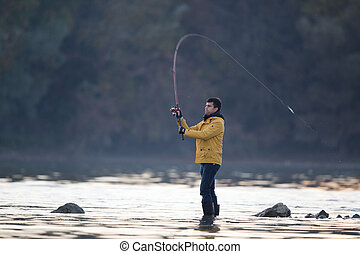 Man fishing on river - Young man fishing on small river in...