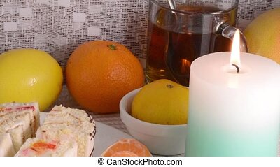 sweet cookies with fruits lemon orange apple tea and candles