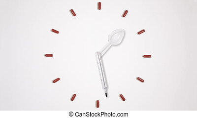 Clock of twelve pills, medical thermometer and plastic...