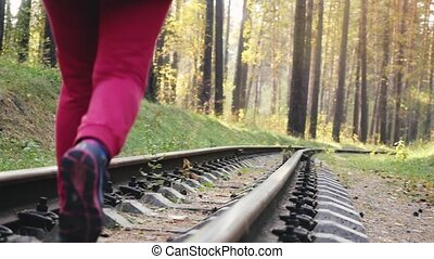 Woman running on railroad in deep pines forest in slow...