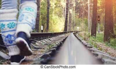 Woman with backpack walking on railroad in deep pines forest...