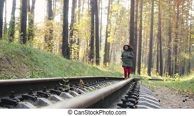 Smiling joyful woman running and jumping on railroad in deep pines forest in slowmotion. 1920x1080