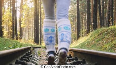 Woman running on railroad in deep pines forest during autumn...