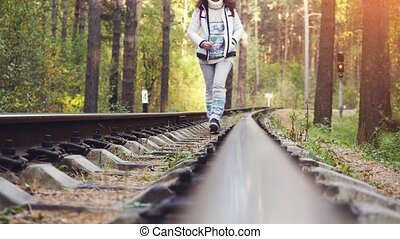 Woman walking on railroad in deep pines forest during autumn...