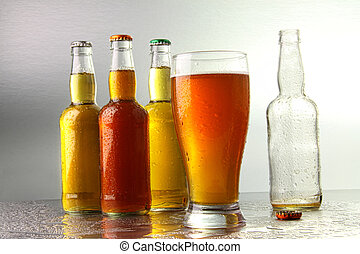 Glass of beer with bottles on stainless counter