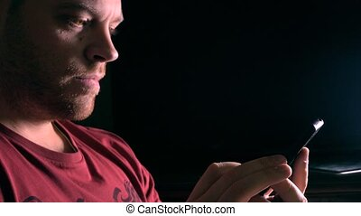 Handsome young bearded man using his mobile phone in dark room 4K video