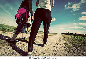 Family walk in countryside on a sunny day. Legs perspective. Vintage look