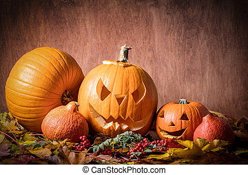 Halloween pumpkins, carved jack-o-lantern in fall leaves....