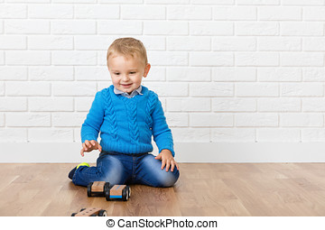 Happy child boy playing with wooden toys on the floor in...
