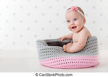 Cute baby sitting happy and laughing in a woollen basket....