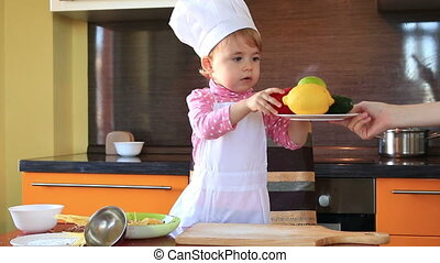 cute little baby dressed as a cook helps mum to prepare a...