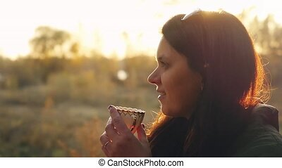 Young beautiful woman having hot tea at sunset relaxing and...