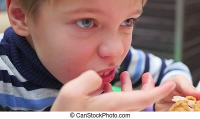child eats fried chicken in a fast food restaurant closeup -...