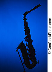 Saxophone Silhouette Against Blue Soptlight - An alto...
