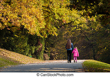 Mother and daughter walk through park in autumn