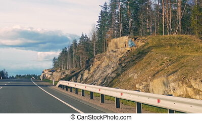 the view from a moving car the road among the woods. Russia,...