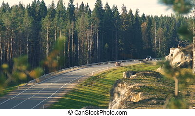 Car driving on an asphalt road in the autumn forest. This...