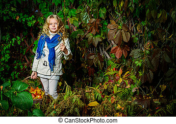 deep forest - Beautiful blonde girl standing with a basket...