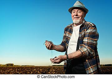 fertile land - An elderly farmer standing in a plowed field....
