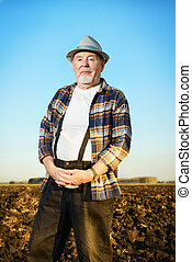 stand on the ground - An elderly farmer standing in a plowed...