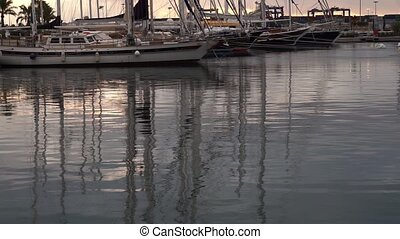 sailboats reflecting on the water of a pier at sunrise