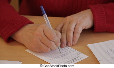 Woman Writing On The form - Woman in red sweater fill in the...