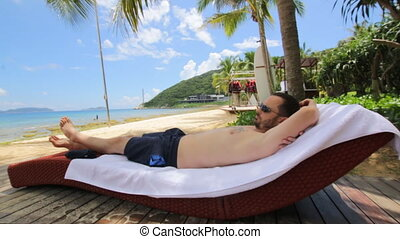 Man relaxing under coconut palm tree on Tropical beach - Man...