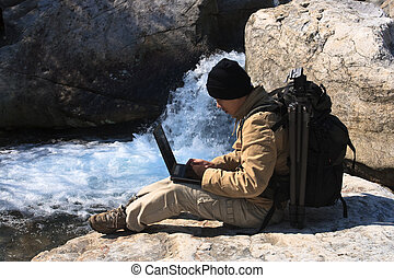 photographer using the laptop by the rivulet outdoor.