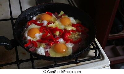 Woman salts fried eggs - Woman pours a seasoning for cooking...