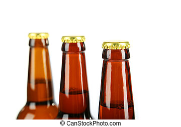 Bottles of beer with drops on white background