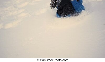 child rolls head over heels with the hill in the snow