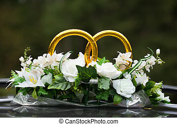 wedding rings on the car with bunch of flowers