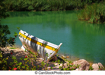 White row-boat resting in the sand on a river shore