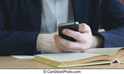 Boy writes the text using a mobile phone indoors
