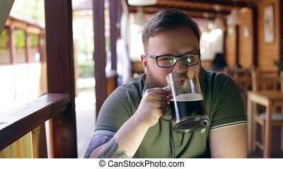 Tattooed, bearded man sitting at the bar on the summer porch, relaxing, looking around and drinking dark beer. TV reflected in his glasses.