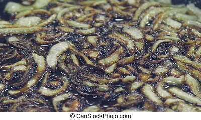 onions fried in vegetable oil in the pan. - Close-up on top...
