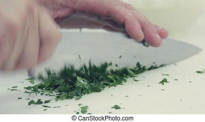 Slowmotion. The chef's knife to cut salading on a cutting Board.