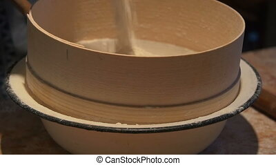 A woman sifts the flour through a sieve