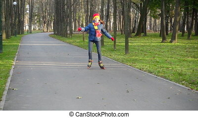 Smiling girl ride in autumn park on rollerblades, slow...