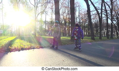 Two little boys ride in autumn park on rollerblades, slow...