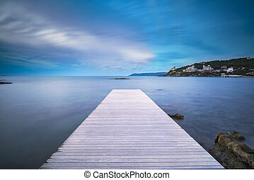 Castiglioncello bay wooden pier, rocks and sea on sunset....