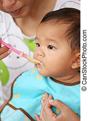 Asian baby boy to eating food in concept of health foods and nutrition.