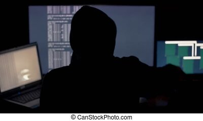 Hacker in hood cracking code using computers in dark room -...