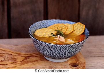 Chicken noodle soup in a blue and white bowl with crackers,...