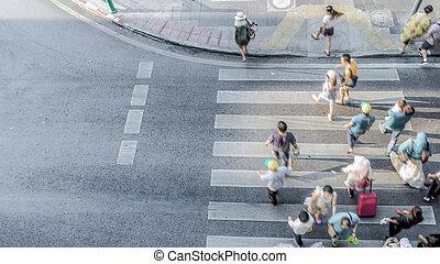 Blur people are moving across the pedestrian crosswalk in...