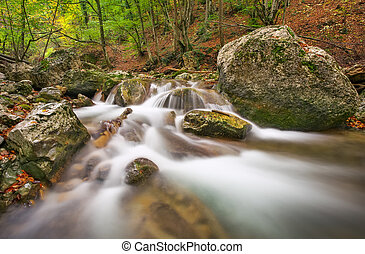Beautiful autumn landscape with mountain river, stones and colorful trees. Mountain forest in Crimea.
