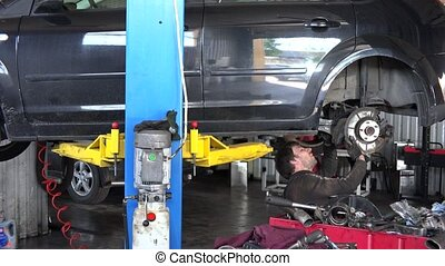 mechanic working under lifted car. close up of tools. focus...